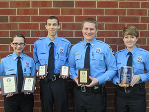 Four police explorer participants in uniform holding plaques