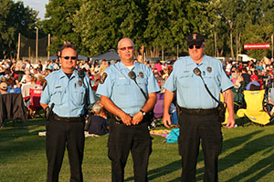 Three police explorers in uniform at outdoor event