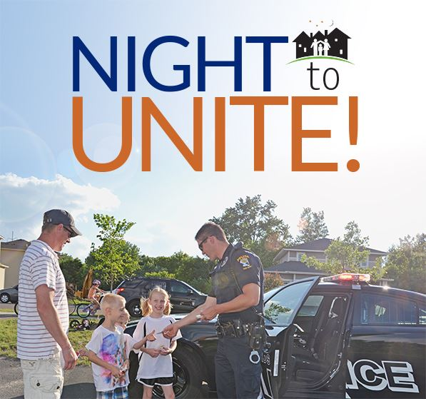 Night to Unite logo above a police officer speaking to children near a squad car