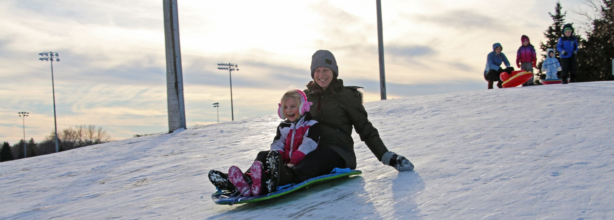 Grandmother and granddaughter sledding down the Wintercrest Park hill.